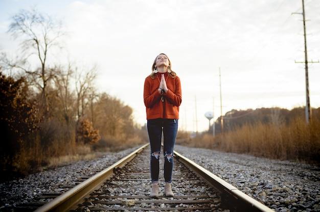 Colpo poco profondo del fuoco di una donna che sta sui binari del treno mentre pregava Foto Gratuite