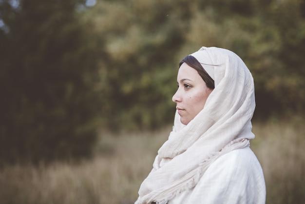 Colpo poco profondo del fuoco di una donna che indossa una veste biblica e guarda in lontananza Foto Gratuite