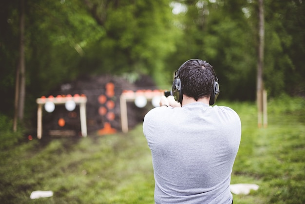 射撃場で銃を撃つ男性の後ろからの浅いフォーカスショット 無料写真