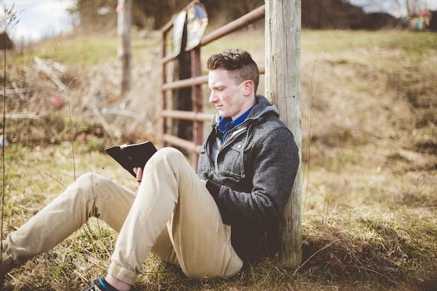 Colpo di fuoco superficiale di un maschio seduto per terra durante la lettura della bibbia Foto Gratuite