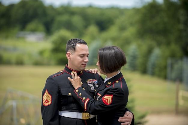 Colpo poco profondo del fuoco di una coppia militare che abbraccia Foto Gratuite