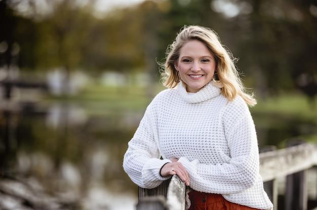 Неглубокий фокус выстрел из женщины, прислонившись к деревянному забору и улыбка на камеру Бесплатные Фотографии