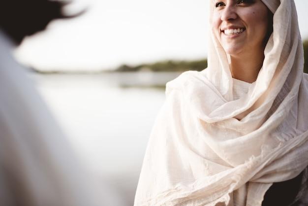 Неглубокий снимок женщины в библейском одеянии, разговаривающей с иисусом христом Бесплатные Фотографии