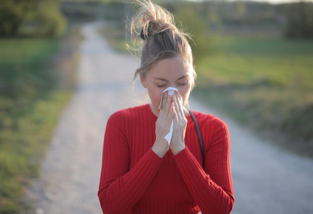 Неглубокий снимок женщины в красной блузке с сезонными аллергическими реакциями Бесплатные Фотографии