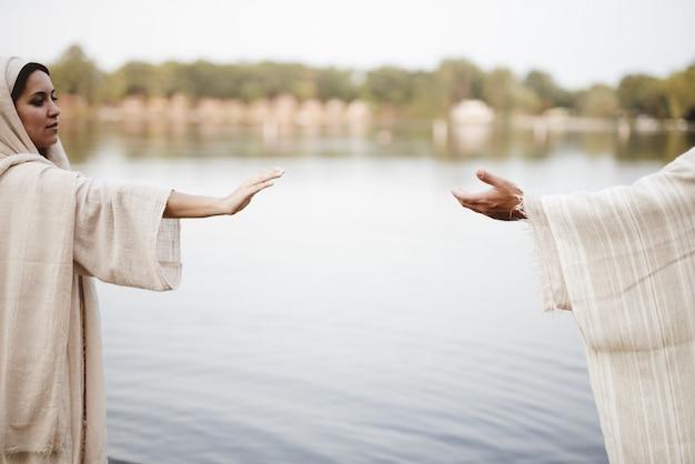 성경의 가운을 착용하고 예수 그리스도의 손을 향해 도달하는 여성의 얕은 초점 샷 무료 사진