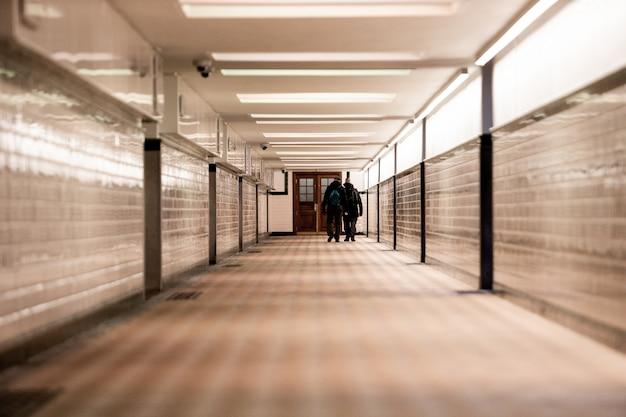 明るい廊下を歩いている2人の男性の浅いフォーカスショット 無料写真