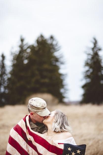 Colpo verticale del fuoco poco profondo di un soldato americano che bacia la sua moglie amorevole Foto Gratuite