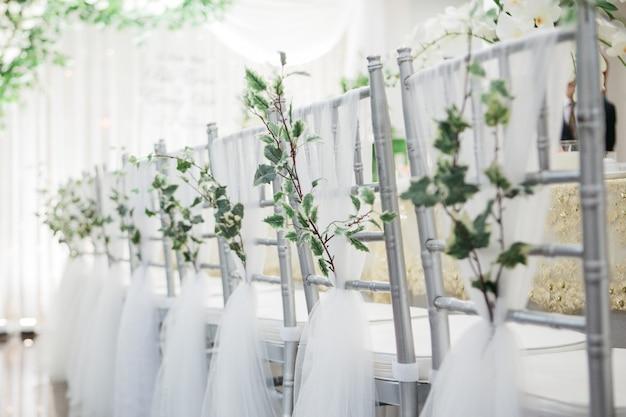 결혼식 테이블 근처에서 결혼식을 위해 장식 된 아름다운 은색 의자의 얕은 초점 샷 무료 사진