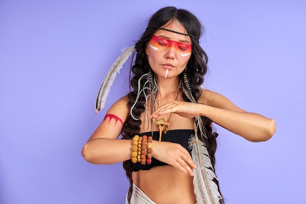 머리카락과 화려한 페인트 메이크업에 인도 깃털을 가진 무속 여성 프리미엄 사진