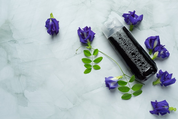 Shampoo bottle of butterfly pea flower put on white marble background Free Photo