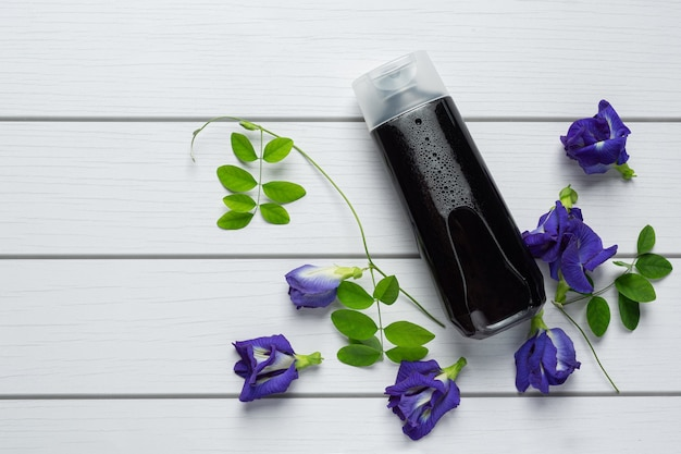 Shampoo bottle of butterfly pea flower put on white wooden background Free Photo