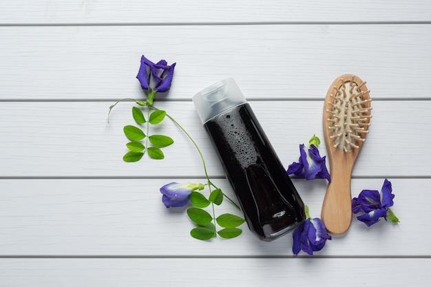 白い木製の背景に置かれた蝶エンドウ豆の花のシャンプーボトル 無料写真