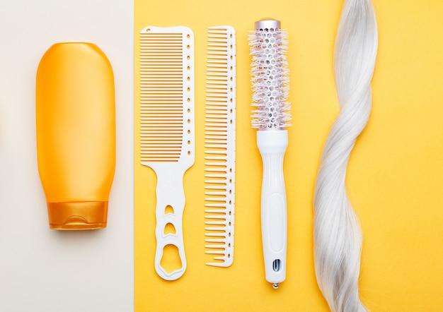 Шампунь, прядь светлых волос, разные расчески на цветном фоне Premium Фотографии