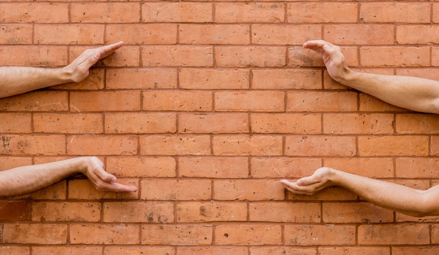 Shape made by human hands on brick wall Free Photo