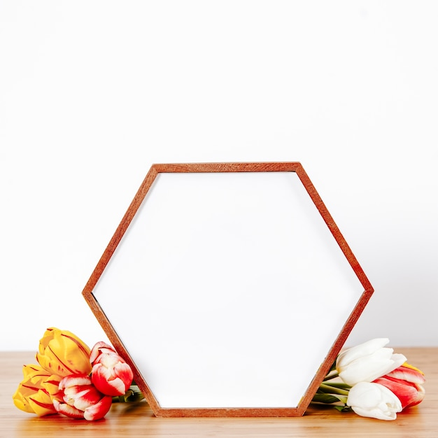 Shaped photo frame with flowers in composition Free Photo