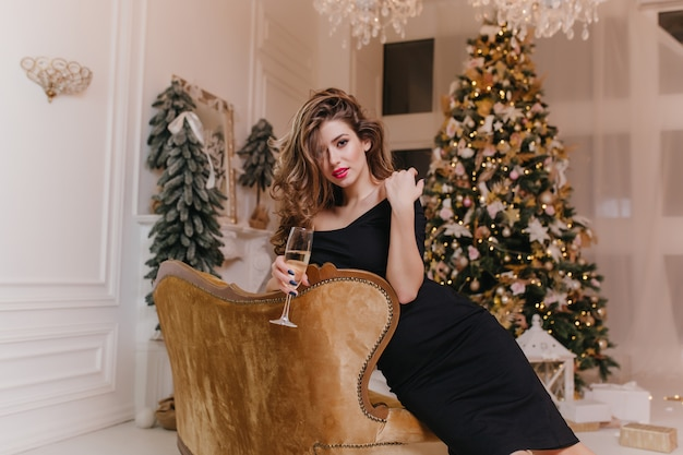 Shapely brown-haired woman relaxing on arm-chair with wineglass in front of christmas tree. elegant caucasian lady in black dress waiting friends on new year party. Free Photo