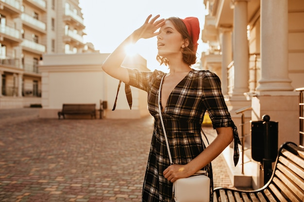 Formosa ragazza in elegante abito grigio guardando a distanza. outdoor ritratto di adorabile signora dai capelli corti in berretto rosso. Foto Gratuite