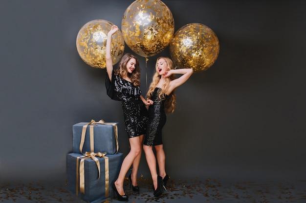 생일 화보 촬영 중 여동생과 장난 치는 긴 곱슬 머리의 매끈한 소녀. 파티를 기다리고, 선물 근처에 서있는 트렌디 한 드레스에 매혹적인 숙녀. 무료 사진