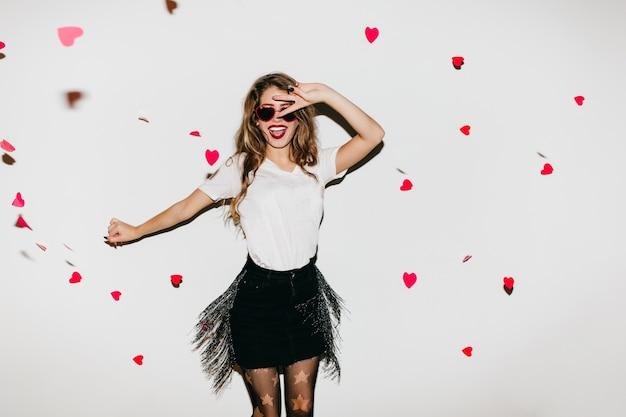 Стройная счастливая женщина прыгает в студии, украшенной сердечками Бесплатные Фотографии