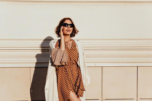 彼女の眼鏡に触れるヴィンテージドレスの格好の良い女性。茶色の服を着て興味のあるリラックスした女の子の屋外ショット。 無料写真