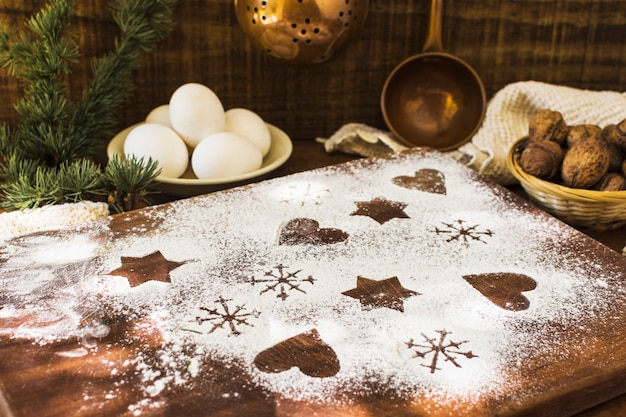 Shapes in flour near ingredients and conifer twig Free Photo