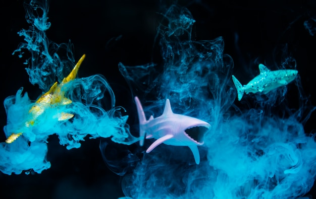 Shark figures in water with negative effect and blue smoke Free Photo