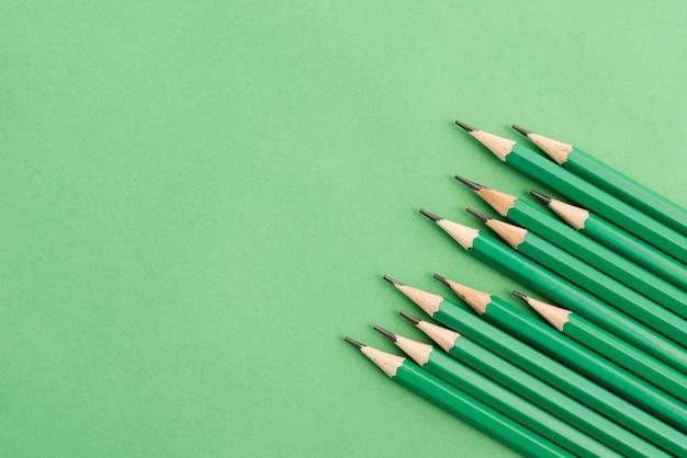 Sharp green pencil at the corner of plain background Premium Photo