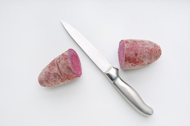 Sharp knife cut half purple sweet potatoes on white background. Premium Photo