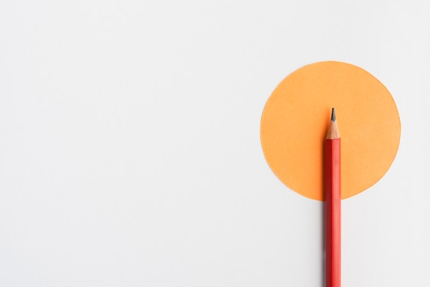Sharp pencil on round shape orange paper over white backdrop Premium Photo