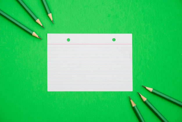 Sharp pencils and line paper textured on bright green background Free Photo