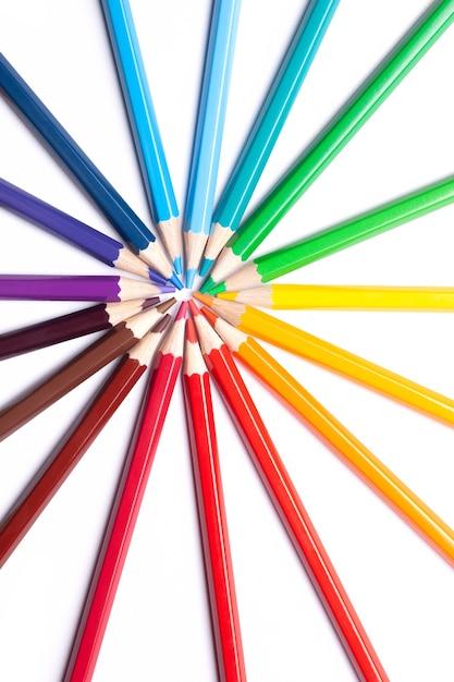 Заостренные цветные карандаши лежат по кругу носиком в центре. Premium Фотографии