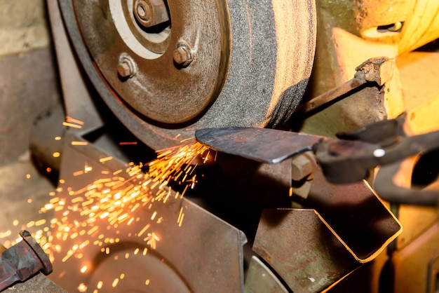 Sharpening iron tools with sparkles - forge workshop Photo