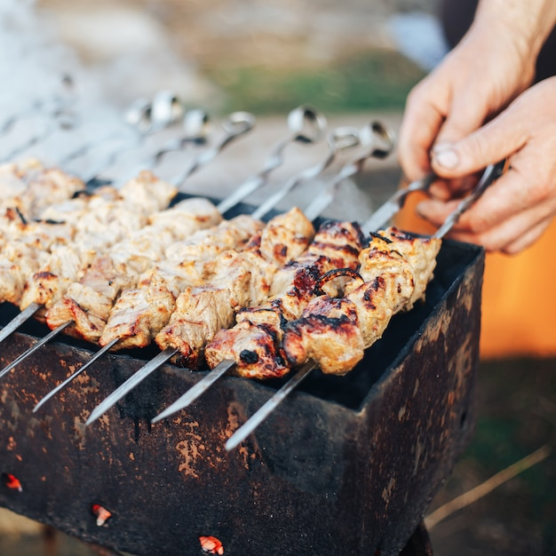 Shashlyk preparing outdoor, man's hands coocking kebab, russian meat in garden Premium Photo