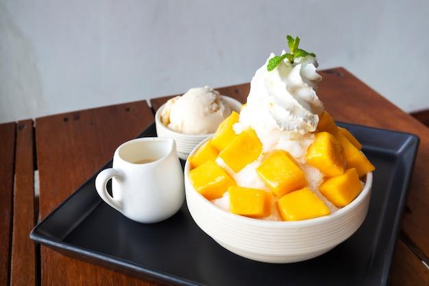 Shaved ice dessert with mango sliced.  served with vanilla ice cream and whipped cream. Premium Photo