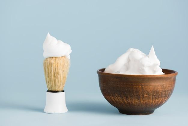 Shaving brush and bowl of foam against blue background Free Photo