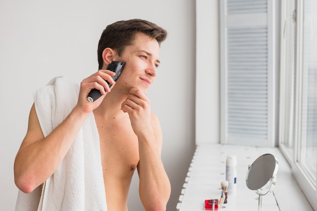 Shaving concept with attractive man Free Photo
