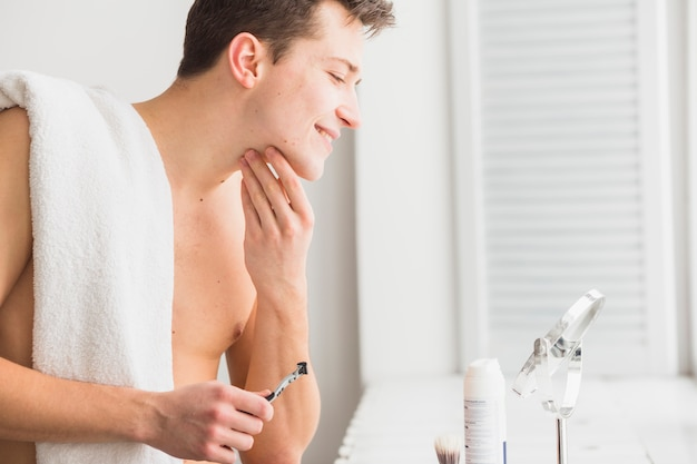 Shaving concept with attractive young man Premium Photo
