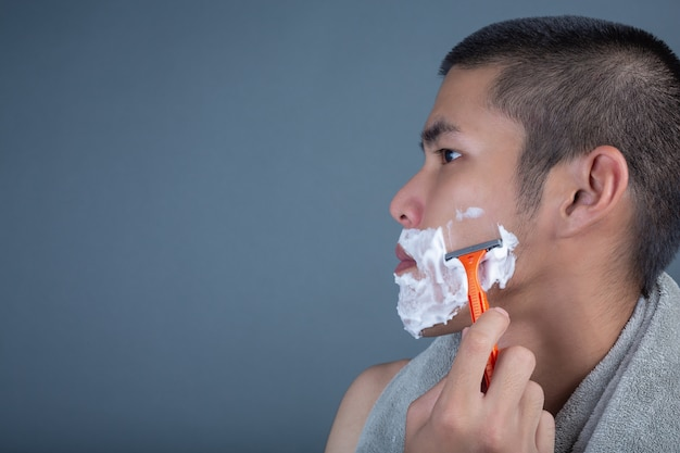 Shaving handsome guy shaved on the face on gray Free Photo