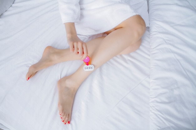 Shaving legs with a razor on a white background. the girl shaves her legs. depilation of the legs with a razor. Premium Photo