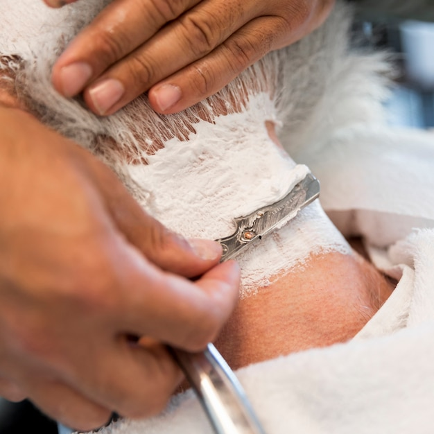 Shaving male neck with straight razor Free Photo