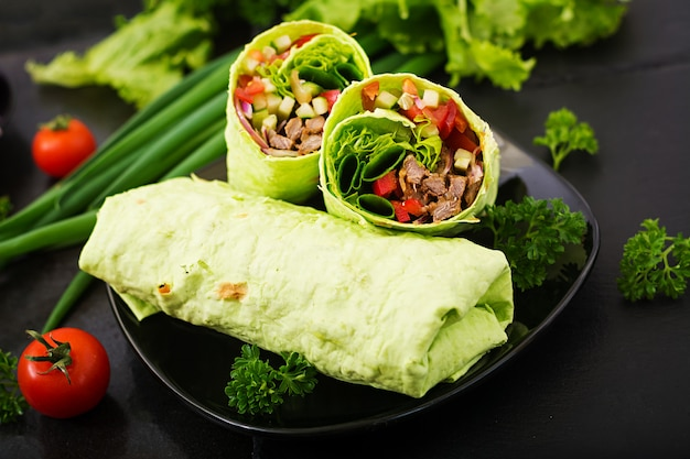 Shawarma from juicy beef, lettuce, tomatoes, cucumbers, paprika and onion in pita bread with spinach. diet menu Free Photo