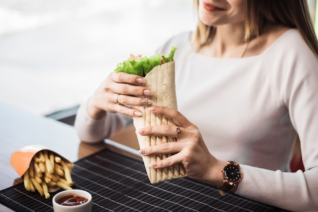 Shawarma, in the hands of a woman. the concept of fast food. pretty woman eating french fries and fa
