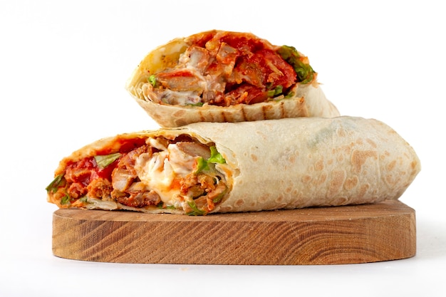 Shawarma, roll in lavash , grilled meat, with vegetables, sandwich , cut on a white background, horizontal, copy spase Premium Photo