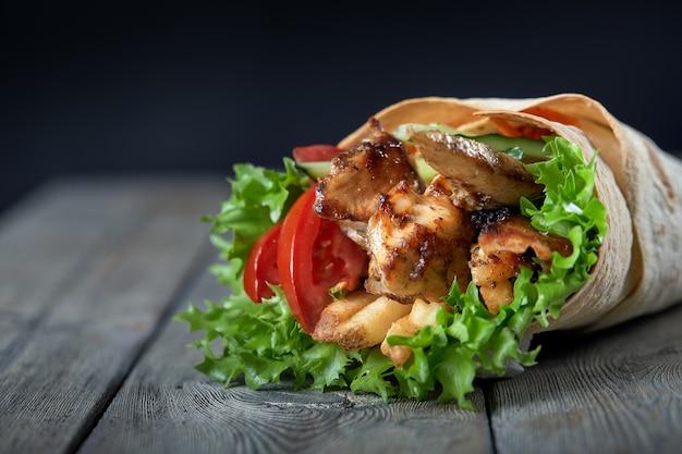 Шаурма, завернутая в лаваш с жареным мясом и овощами на деревянном фоне Premium Фотографии