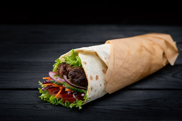 Shawarma rolled in lavash, moist grilled meat with onion, herbs and vegetables on wooden black background. Premium Photo