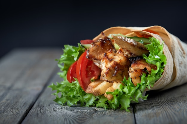 Shawarma rolled in lavash with grilled meat and vegetables on wooden background Premium Photo