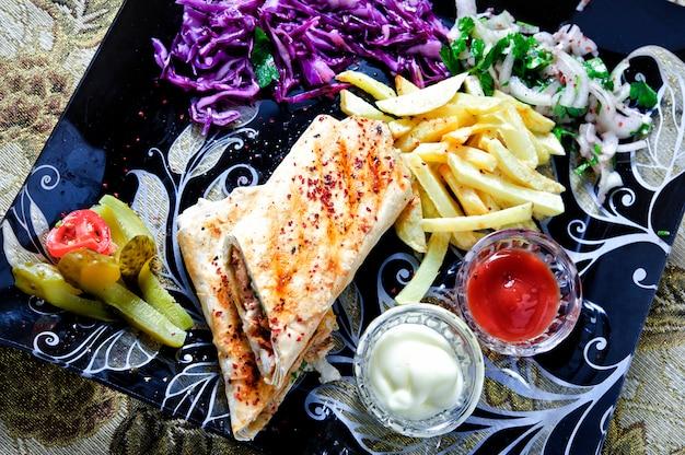 Сэндвич с шаурмой свежий рулет из лаваша (лаваша) с куриной говядиной и шаурмой традиционная ближневосточная закуска. Premium Фотографии