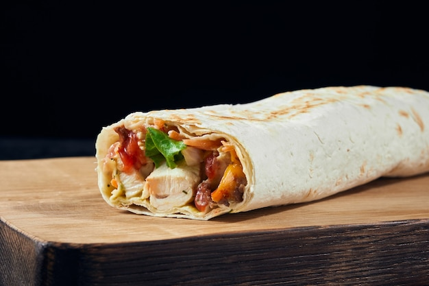 Shawarma sandwich. fresh roll of thin lavash filled with chicken meat, cheese, sauce, green on wooden board. traditional eastern snack. Premium Photo