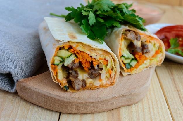 Шаурма с начинкой из мяса на гриле, соусом, овощами Premium Фотографии