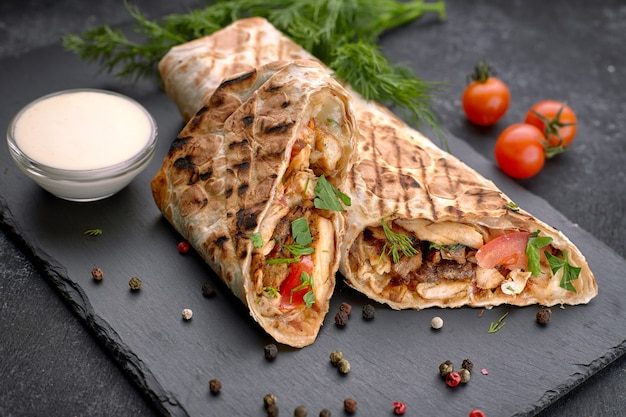 Shawarma with meat, cutaway, with sauce, tomatoes, cheese, herbs and garlic, on black slate, on a black background Premium Photo